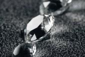 Nahaufnahme reiner Diamanten auf grau strukturiertem Hintergrund