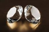 Fotografie Nahaufnahme klarer Diamanten auf goldenem, dunklem Hintergrund
