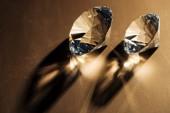 Fotografie funkelnde klare Diamanten auf braunem Hintergrund, die Licht reflektieren