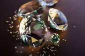 Fotografie Selektivní fokus jasné diamantů na hnědé pozadí