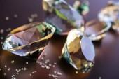 Selektivní fokus velkých i malých diamantů na hnědé pozadí