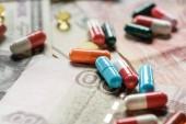 zblízka vícebarevné různých pilulek na pozadí peníze