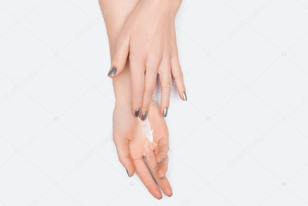 Cropped view of woman applying hand cream isolated on white