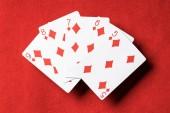 pohled shora červené pokerového stolu a nepřeložené hrací karty s diamanty suit
