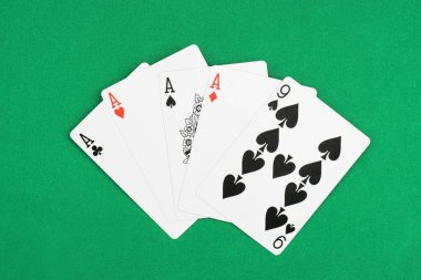 top view of green poker table with unfolded playing cards, four aces and nine