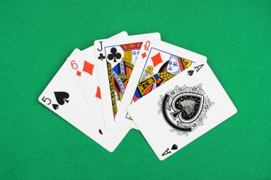 top view of green poker table with unfolded playing cards diamonds, spades and clubs suits