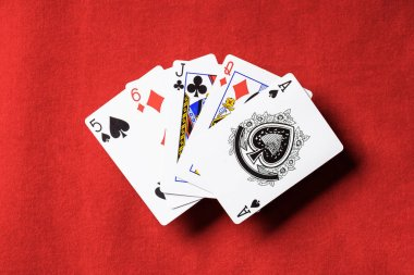 top view of red poker table and unfolded playing cards with different suits