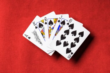 top view of red poker table and unfolded playing cards with spades suit