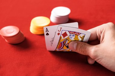 selective focus of man holding playing cards with chips on background