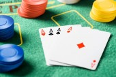 selective focus of green poker table with four aces playing cards and chips