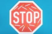 Studioaufnahme von Stoppschild und Zigaretten isoliert auf blau, Raucherentwöhnungskonzept