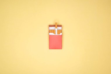 Studio shot of red pack of cigarettes isolated on yellow