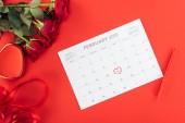 Fotografia vista superiore di rose e calendario con 14 febbraio data contrassegnata con cuore isolato su colore rosso, San Valentino concetto