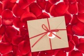 Fotografie top view of envelope with ribbon and red rose petals on background, st valentines day concept