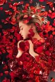 Fotografia vista superiore della bella ragazza che tiene il simbolo del cuore con cuore a forma di coriandoli isolato sul nero, concetto di San Valentino
