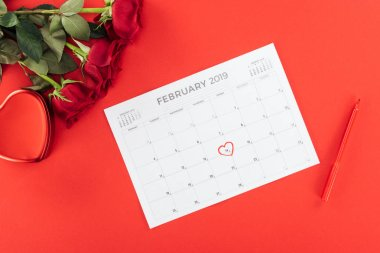 Top view of roses and calendar with 14th february date marked with heart isolated on red, st valentines day concept stock vector