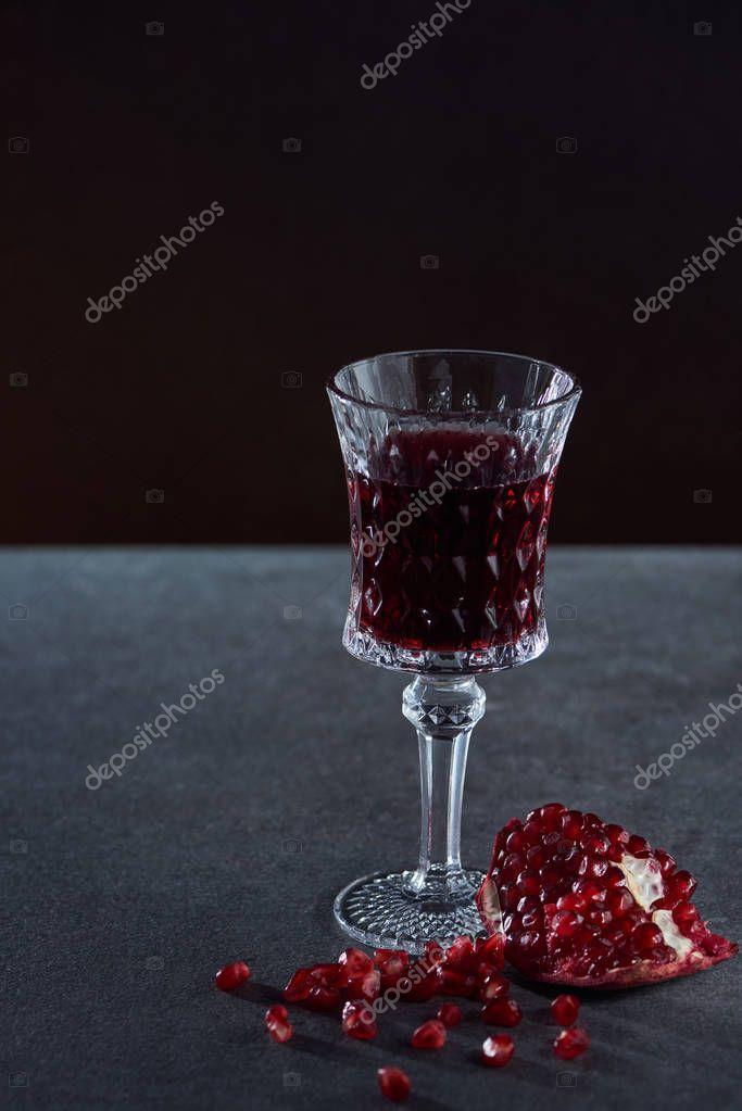 Studio shot of vintage wineglass with garnet on dark background stock vector