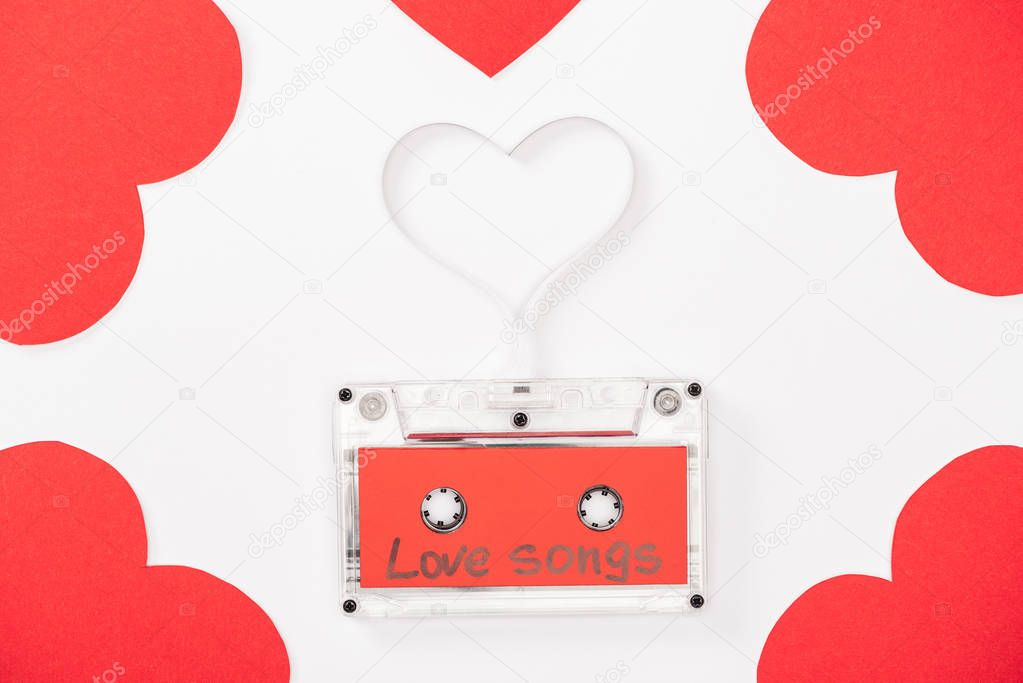Top view of audio cassette with 'love songs' lettering and heart shaped cards isolated on white, st valentines day concept stock vector