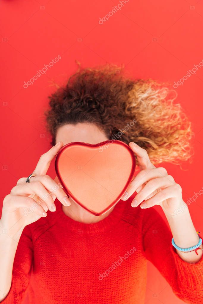 Top view of girl holding heart symbol in front of face isolated on red, st valentines day concept stock vector
