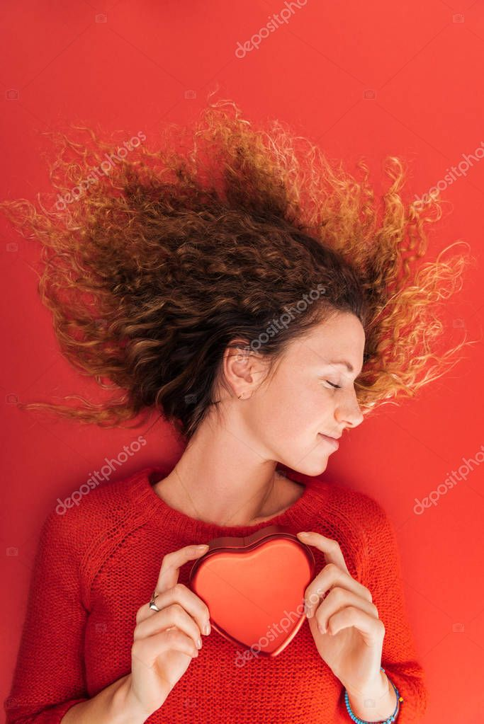 Top view of beautiful girl holding heart symbol isolated on red, st valentines day concept stock vector