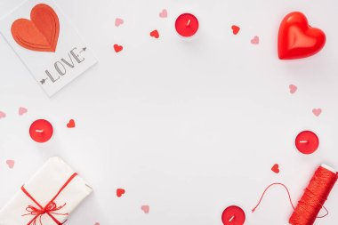 Top view of gift box, paper hearts and greeting card with 'love' lettering isolated on white with copy space, st valentines day concept stock vector