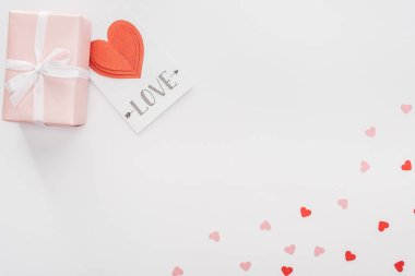 Top view of gift box, paper hearts and greeting card with 'love' lettering isolated on white, st valentines day concept stock vector