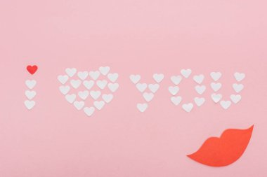 top view of 'i love you' lettering made of paper hearts isolated on pink, st valentines day concept