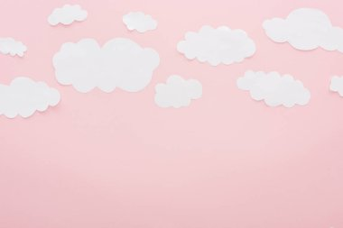 top view of white paper clouds isolated on pink with copy space