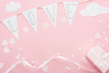 Top view of paper garland with 'love' lettering and gift box isolated on pink, st valentines day concept stock vector