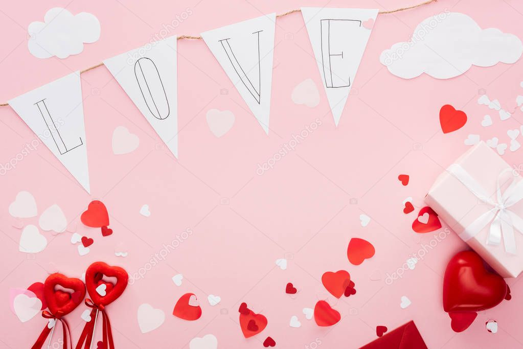 Top view of valentines decorations and paper garland with 'love' lettering isolated on pink with copy space, st valentines day concept stock vector