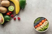 top view of smoothie bowl with fruits and fresh ingredients on grey background