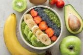 Fotografie pohled shora smoothie lahodné mísa s čerstvým ovocem a ingredience na šedém pozadí