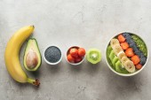 Fotografie top view of healthy smoothie bowl with fresh fruits and ingredients on grey background