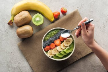 top view of woman holding spoon over smoothie bowl with fresh fruits on grey background