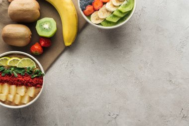 top view of smoothie bowls with fresh fruits and organic ingredients on grey background with copy space