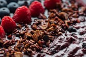 Photo selective focus of blueberries, raspberries and homemade granola in smoothie bowl