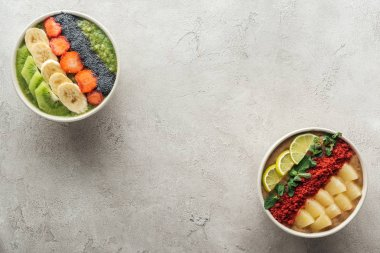 top view of healthy organic smoothie bowls with fruits on grey background with copy space