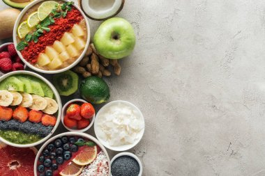 top view of healthy smoothie bowls with ingredients on grey background