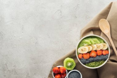 top view of smoothie bowl, wooden spoon and ingredients on grey background with copy space