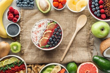 top view of smoothie bowls with wooden spoon and frame made of fresh ingredients on sackcloth