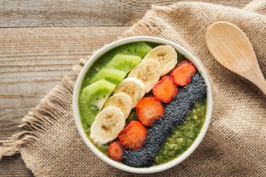 top view of fresh smoothie bowl on sackcloth and wooden background