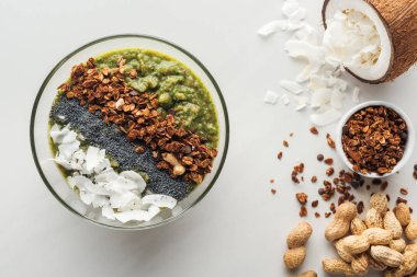 top view of fresh green smoothie bowl with ingredients on white background