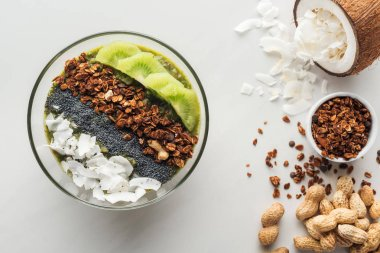 top view of healthy green smoothie bowl with ingredients on white background