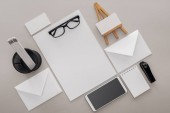Photo flat lay with blank cards, glasses, smartphone and stationery on grey background