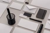 Fotografia lay flat con forniture per ufficio bianco e nero su sfondo grigio