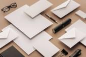 Fotografia Occhiali, fogli di carta, carte, penna, taccuino, cucitrice su fondo beige