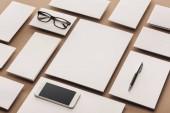 Fotografia Piatto posare con smartphone, occhiali, penna, carte e fogli di carta