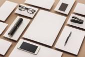 Prázdné listy papíru, případ, brýle, smartphone, pero a sešívačka na béžové pozadí