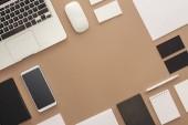 Fotografia Laptop, smartphone, penna, mouse del computer, carte e quaderni su fondo beige