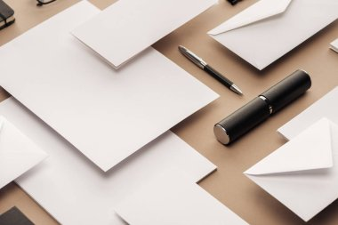 Pen, case, envelopes and sheets of paper on beige background